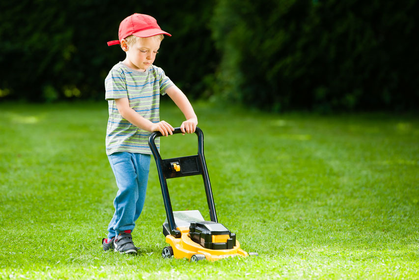 Picture of boy mowing grass.